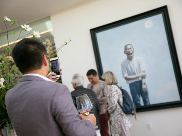 A man takes a photograph of a painting while holding a glass of wine.